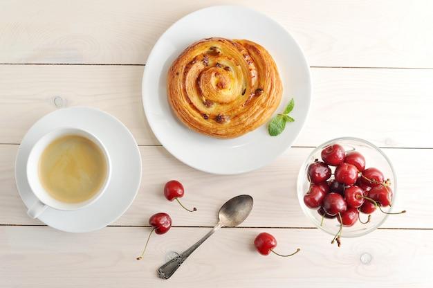 Caffè in una tazza, cupcake con ciliegie alla cannella su fondo di legno rustico bianco