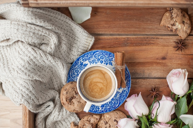 Caffè in una tazza d'epoca su uno sfondo di legno e un mazzo di rose bianche.