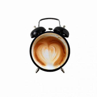 Caffè late art e sveglia nera