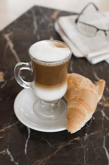 Caffè latte con cornetto e bicchieri sfocati
