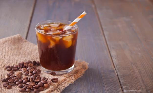 Caffè latte ghiacciato con cubetti di ghiaccio e chicchi di caffè su un tavolo.