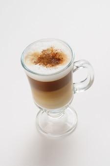 Caffè latte in una tazza su una superficie bianca