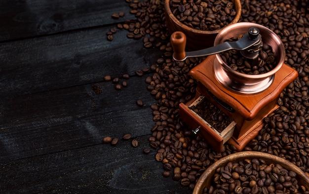 Caffè macinato, macinacaffè, ciotola di chicchi di caffè arrostiti su fondo di legno nero, vista superiore