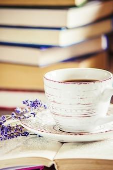 Caffè mattutino sul posto di lavoro. con un libro o un laptop. messa a fuoco selettiva.