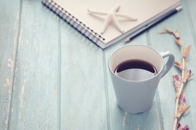 Caffè nero con il taccuino e matita su fondo di legno, tono d'annata fuoco molle