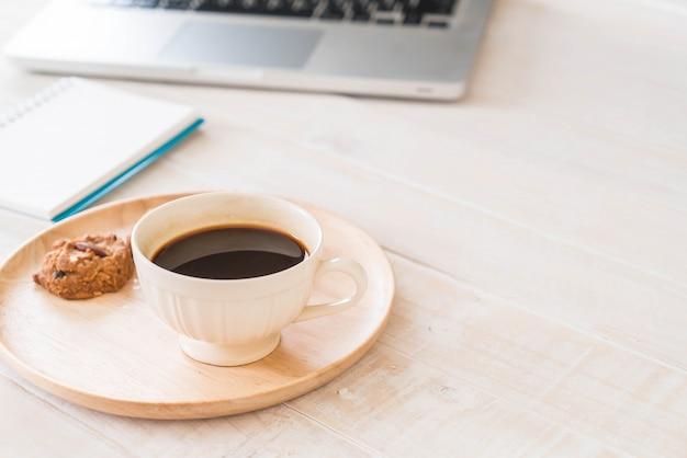 Caffè nero e biscotti con il computer portatile e il taccuino