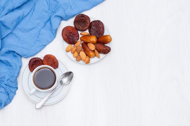 Caffè nero e frutti secchi su bianco con la tovaglia