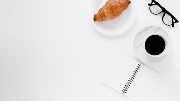 Caffè nero e taccuino del croissant con lo spazio della copia