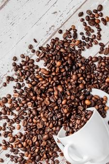 Caffè nero in tazza bianca e chicchi di caffè su fondo di legno leggero.