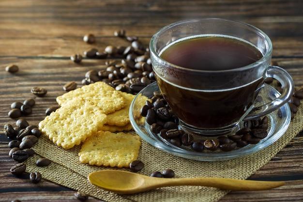 Caffè nero in tazza di vetro trasparente con chicchi di caffè e cracker disposti su una stuoia di canapa.