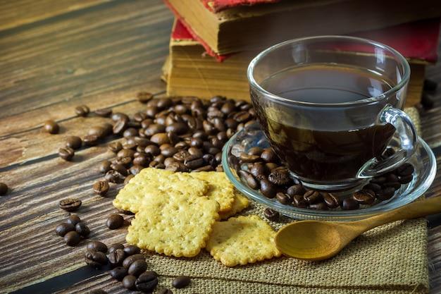 Caffè nero in tazza di vetro trasparente e chicchi di caffè con cracker e vecchio libro sul tavolo di legno.