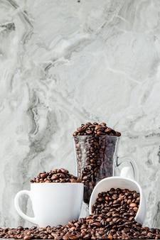 Caffè nero in tazza e chicchi di caffè su fondo di marmo.