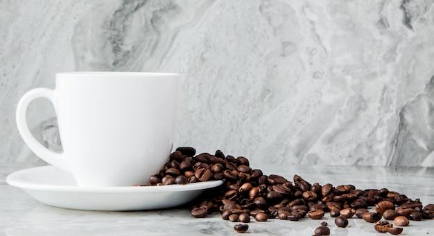 Caffè nero in tazza e chicchi di caffè