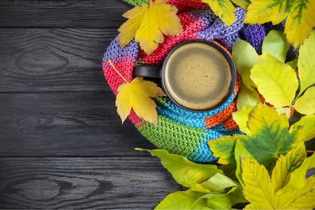 Caffè nero in una tazza nera avvolta in una sciarpa calda, colorata, lavorata a maglia e foglie d'autunno
