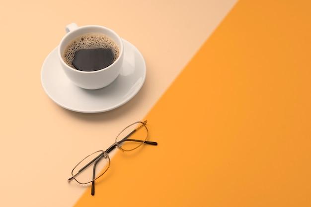 Caffè nero sul piatto e occhiali su sfondo colorato con spazio di copia