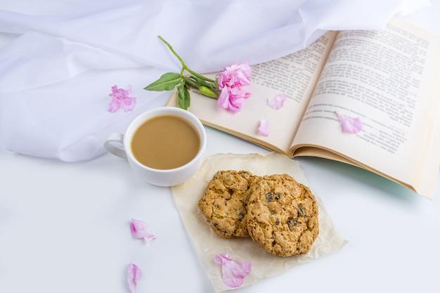 Caffè o tè con biscotti al latte e avena. leggere un vecchio libro e uno spuntino in primavera, giorno d'estate in giardino