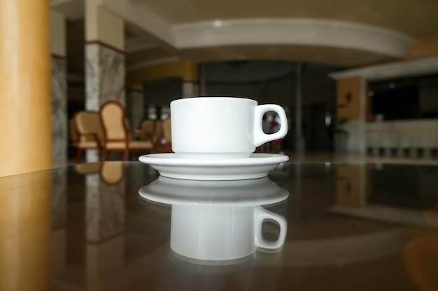 Caffè o tè in una tazza bianca e piattino. l'hotel è tutto compreso. rompi nella sala d'aspetto.