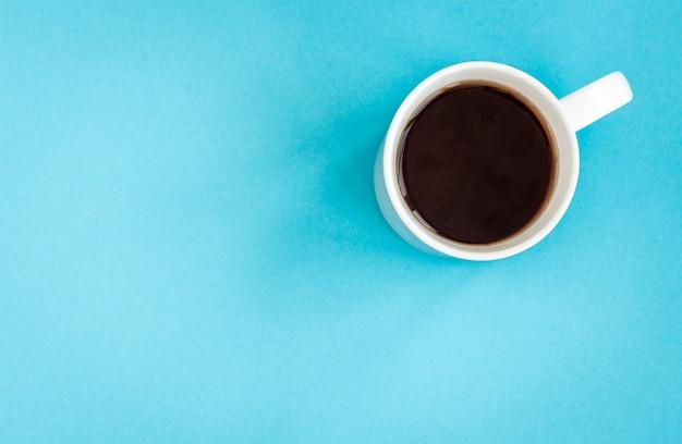 Caffè o tè nero in tazza bianca sull'azzurro.