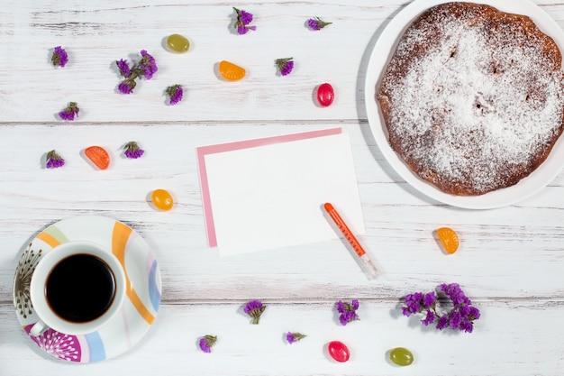 Caffè, pasticceria, fiori e carta in bianco sul tavolo di legno