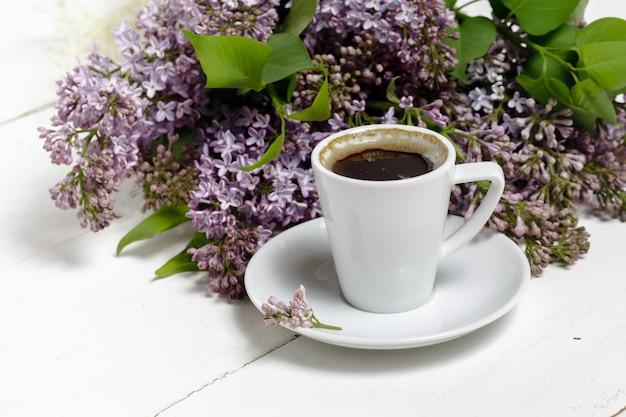 Caffè per colazione e fiori lilla. messa a fuoco selettiva