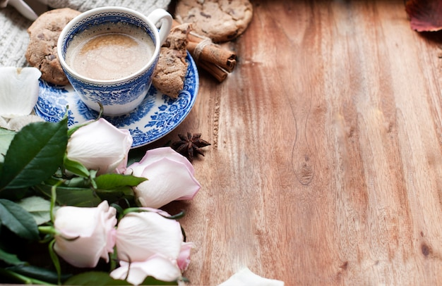 Caffè romantico in una tazza su uno sfondo di legno con un plaid, un bouquet di rose bianche e intimità d'autunno. buongiorno. vista dall'alto. copia spase