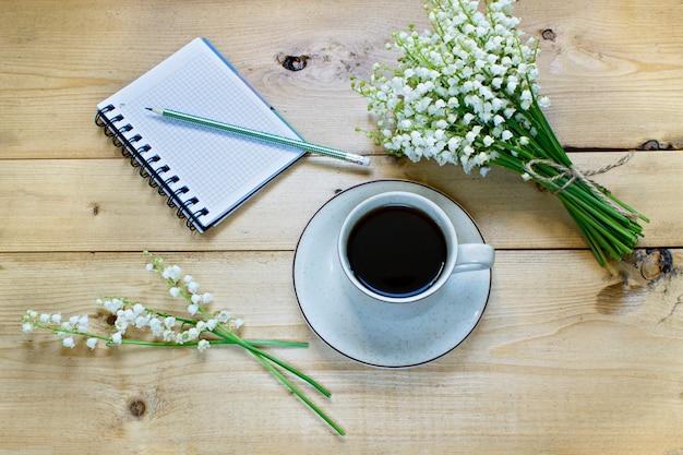 Caffè su uno sfondo in legno e fiori.