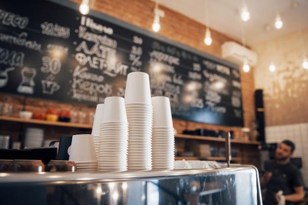 Caffetteria dall'aspetto hipster pronta per essere aperta al giorno con un bancone pulito e ordinato e una macchina da caffè lucida ben mantenuta sulla superficie in legno