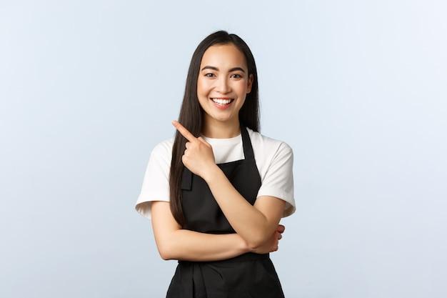Caffetteria, piccola impresa e concetto di startup. la femmina asiatica allegra che lavora a tempo parziale al caffè, indossa il grembiule nero, indica l'angolo in alto a sinistra del dito, l'invito vede l'insegna o la pubblicità