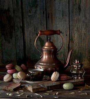 Caffettiera in rame vintage, tazza di caffè nero e maccheroni colorati su fondo di legno rustico.
