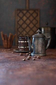 Caffettiera vintage e gocce di cioccolato su sfondo scuro