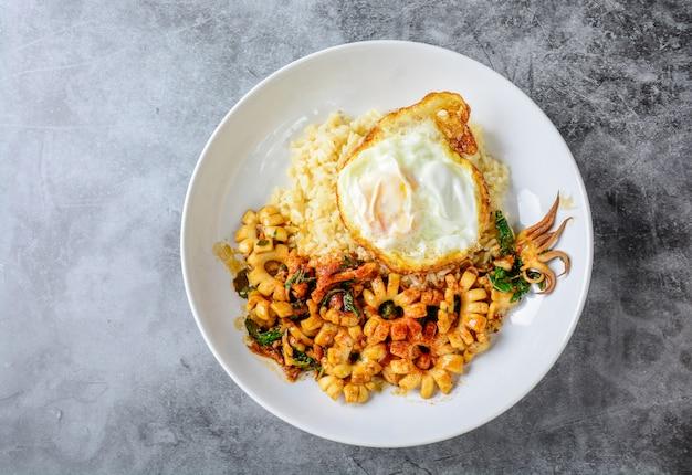 Calamari fritti scalpore piccanti con foglie di basilico e peperoncino, uovo di sunny side up, servito con riso integrale