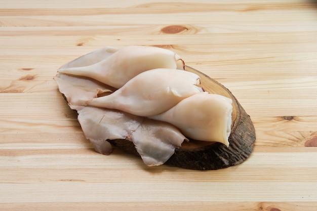 Calamari pilled congelati sulla tavola di legno