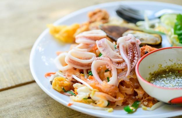 Calamari su spaghetti di riso saltati in padella (pad thai) con cozze.