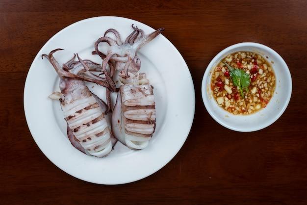 Calamaro alla griglia con salsa di immersione sul piatto bianco