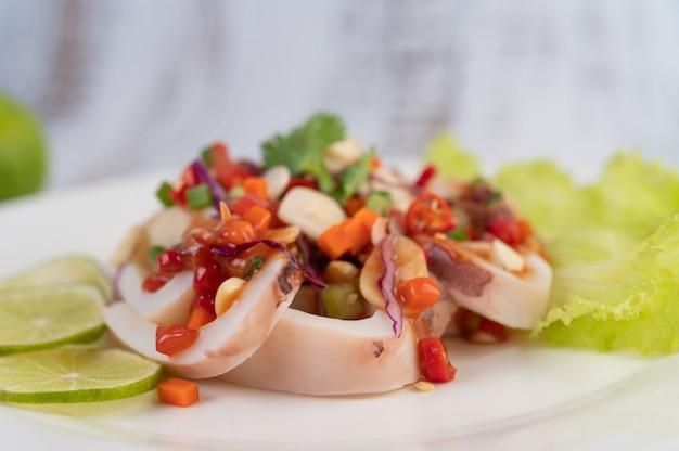 Calamaro piccante al limone con galanga, peperoncini rossi, carote, menta piperita, cipollotti e aglio su un piatto su un pavimento di legno bianco.