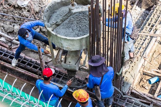 Calcestruzzo di versamento del lavoratore che versa nella cassaforma di fondazioni a zona di costruzione nel cantiere.