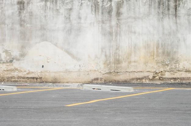 Calcestruzzo vecchio e sporco del primo piano con il pavimento della strada al fondo di struttura del parcheggio