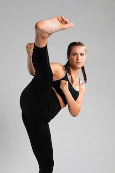 Calcia di una donna in forma in posizione di combattimento