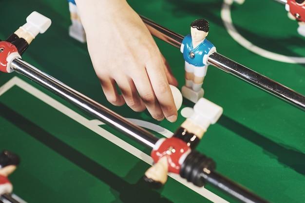 Calcio balilla nel centro di intrattenimento. immagine ravvicinata di una ragazza che lancia una palla giocattolo in una partita di calcio