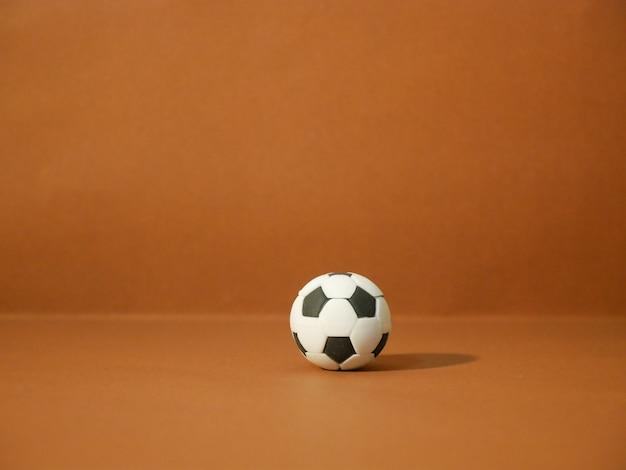 Calcio di calcio con lo spazio della copia su fondo marrone