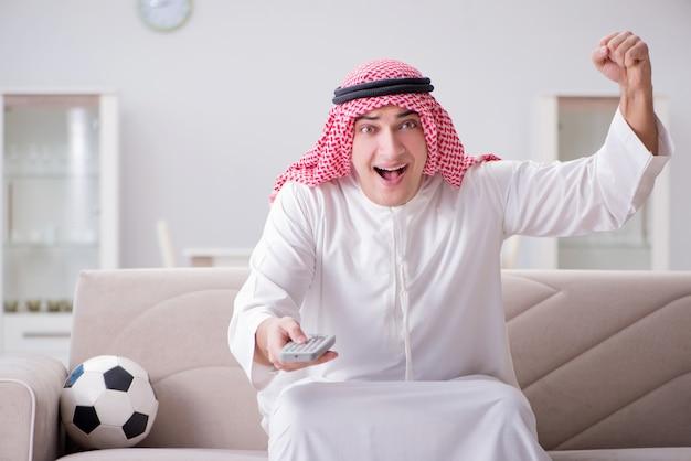 Calcio di sorveglianza del giovane uomo arabo che si siede sul sofà