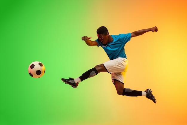 Calcio maschile, allenamento del giocatore di football in azione isolato su studio sfumato in luce al neon