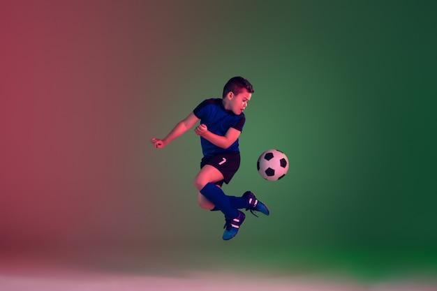 Calcio o calciatore maschio teenager, ragazzo sul fondo di pendenza alla luce al neon - moto, azione, concetto di attività