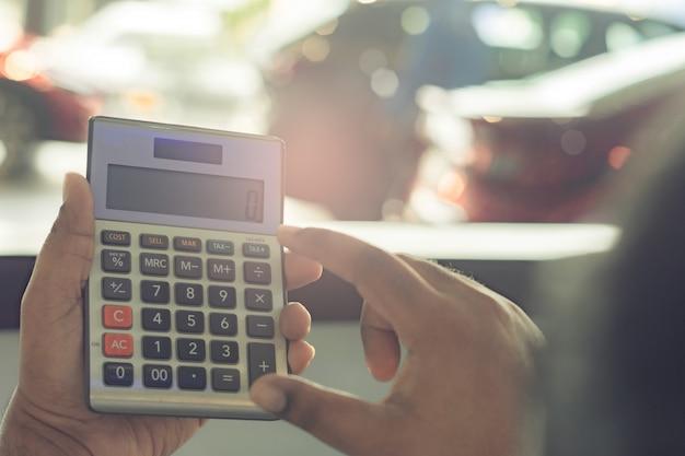 Calcolatore asiatico della tenuta dell'uomo per finanza di affari sul fondo del bokeh vago sala d'esposizione dell'automobile per l'automobile automobilistica o il trasporto del trasporto