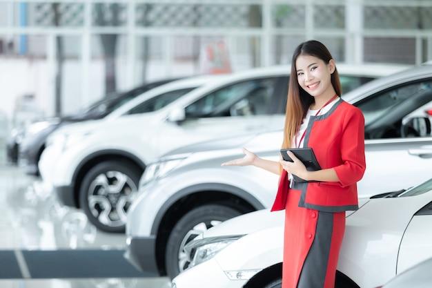 Calcolatore asiatico della tenuta della venditora di giovane automobile con un'esposizione benvenuta in sala d'esposizione.
