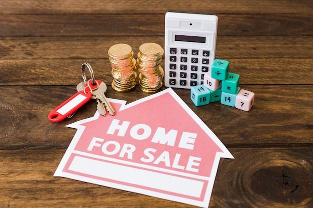 Calcolatore, blocchi matematici, monete impilate e chiave con casa per icona di vendita su fondo di legno