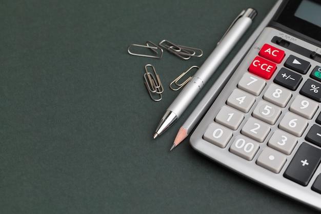 Calcolatore della tavola dell'ufficio con la penna, copyspace nero