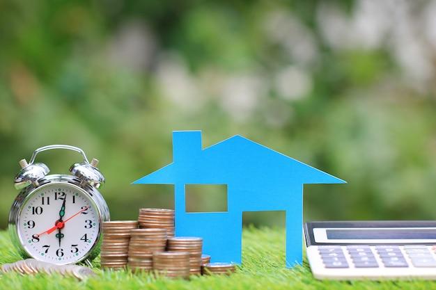 Calcolatore di ipoteca, modello della casa blu e pila di monete soldi con la sveglia, tassi di interesse e concetto di attività bancarie
