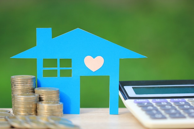 Calcolatore di ipoteca, modello di casa blu e pila di monete di denaro
