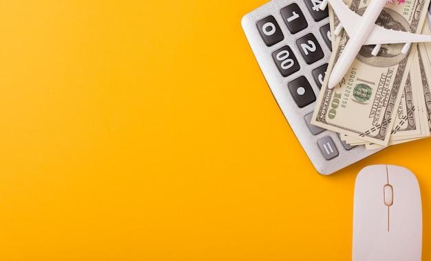 Calcolatrice, aeroplanino giocattolo, mouse e banconote da un dollaro